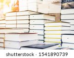 Small photo of Bookstore shelf with pile of new books with red empty plate. New arrivals at bookshop. Presentation of book. Copyspace
