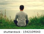 Small photo of A young guy in a light polo sits on the shore. The view from the back. Yoga training. Appeasement