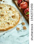 Small photo of Italian fresh four cheese pizza with walnuts on a light background. Composition with pizza, sauce and tomatoes. Top view with copy space. Flat lay. quattro fromaggi