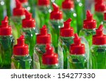 Small photo of Many bottles with abstergent, red cap and green liquid.