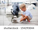 Young Boy Ties Rope To Cleat O...