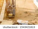 Small photo of worker compresses sand in blind area around building with special working tool (tamping machine or vibratory plate)