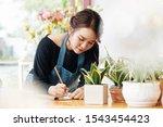 Young Asian Florist Writing...