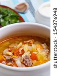 Small photo of Russian traditional cabbage soup - shchi in a ceramic pot