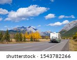 An RV aon the highway through the Canadian Rocky Mountains in Kananaskis, Alberta, Canada during the peak of autumn colors - stock photo