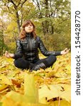 young woman meditates in the autumn park - stock photo