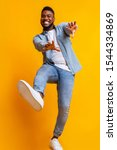 Small photo of Funny african american guy dancing and extending his hands to camera over yellow studio background, low-angle view