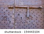 Old and rusty metal door with many keyholes and antique door latch - stock photo