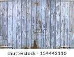 Old, grunge wood panels of wide light blue door - stock photo