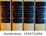 "Small photo of Albi, France - Oct. 2019 - ""Encyclopaedia Universalis"" written in golden letters in the French-language version ; some volumes of the encyclopedic dictionary in the bookshelf of a library"