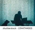 Stock photo silhouette on turquoise office curtain of a sitting man working with laptop computer with his dog 1544744003