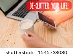 Small photo of Text sign showing De Clutter Your Life. Conceptual photo remove unnecessary items from untidy or overcrowded places woman laptop computer smartphone mug office supplies technological devices.