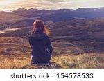 Woman Sitting On Mountain Top...