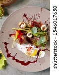 Small photo of Exquisite serving vintage plate of turkey meat roulade or meatloaf with aronia sauce, barberry berries, plums and cheese. Autumn restaurant menu decorated with edible flowers and nasturtium leaves