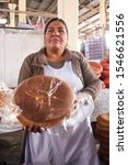 Small photo of Women offering Pan Chuta bread: hand made tradition, symbology and taste of Andes sacred mountains. Cusco, Peru, Oct, 2019.