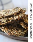 Small photo of Homemade crispy gluten free flatbread cracker with lots of seeds and psyllium on white background. Healthy snack, seed crackers - horizontal image