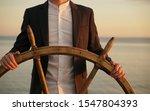 Businessman Holding Ship Wheel...