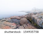 Foggy morning at the rocky coast during late summer with horizon non visible, Sweden - stock photo
