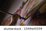 Artist designer draws an eagle on the wall. Craftsman decorator paints a picture with acrylic oil color brush. Close-up dark magic cinematic look. Painter dressed in a paint coat. Indoor.