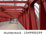 Small photo of Pedestrian crossing, construction of red metal structures. The roof is made of steel channels connected to each other. Red iron beams on bolts and rivets.