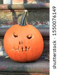 Small photo of Halloween pumpkin on a stoop in the crown heights section of Brooklyn on a sunny fall day in Brooklyn NY October 4 2019