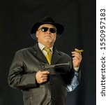 Small photo of A man in black clothes, a black leather coat, hat. Ganster with a cigar Mauser system pistol. Mafiosi in black glasses on a dark background. Severe, strong, stylish, impressive, dangerous, unfriendly