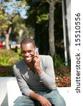 a handsome african american man laughs and talks on his cell phone - stock photo