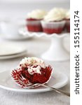 Half eaten red velvet cupcake with creamcheese frosting - stock photo