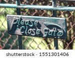An Old Gate With A Green Sign...