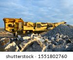 Small photo of Mobile Stone crusher machine by the construction site or mining quarry for crushing old concrete slabs into gravel and subsequent cement production. Jaw crusher with conveyor belt