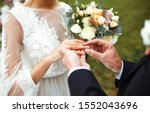 Small photo of Wedding engagement rings. Married couple exchange wedding rings at a wedding ceremony. Groom put a ring on finger of his lovely wife. Concept wedding details. Happy family. Together.