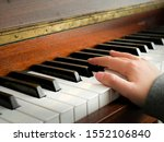 Small photo of Teenager hand on piano keys, grey sleeves , Concept music practice, training, developing fluent hand movement.