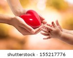 Small photo of life in your hands - heart whit orange background