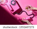 Small photo of Cropped view of woman holding cocktail and telephone handset beside astray with cigarette butts on pink surface