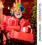 Small photo of Hocus pocus. Christmas spirit. Cheerful clown colorful hairstyle. Party entertainment. Winter holidays. Christmas decorations home. Bearded senior man celebrate christmas. Mature man with white beard.