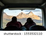 Two people lying in a camper van looking out towards the mountains during sunset Durmitor National Park - stock photo