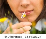 A Woman Is Holding A Daisy Nea...