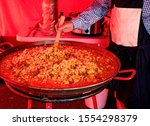 Small photo of Man stirring a large pan of bubbling hot and delicious savory paella at a market stall