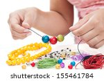girl's hands making a necklace... | Shutterstock . vector #155461784