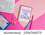 Conceptual hand writing showing Raising The Stakes. Business photo showcasing Increase the Bid or Value Outdo current bet or risk Writing equipments and computer stuff placed on plain table. - stock photo