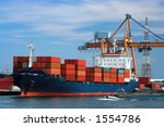 Large container ship in a dock at Antwerp harbor (logos and brandnames systematically removed) - stock photo