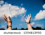 Some one trying to catch soap bubbles. Hands trying to catch  floating soap bubbles