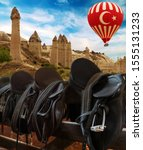 Small photo of Love valley mountain phallus landscape ballooning fly tour. Rider Leather Saddles on fence. Balloons Turkish flag flying over Cappadocia, Goreme, travel Turkey.