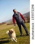 Stock photo man taking dog on walk in autumn countryside 155572298
