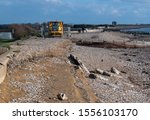 Small photo of Climping Beach, West Sussex, UK, November 10, 2019, Sea footpath undermined and washed away after a major winter storm, large repair vehicle waiting to repair the damage.