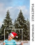 Small photo of Charming boy in a clownish cap of Santa Claus smiles through a white frame. Giau Pass, Dolomite Alps. The first snow. Concept of Christmas and New Year tourism