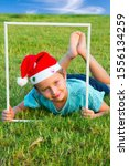 Small photo of Charming boy in a clownish cap of Santa Claus smiles through a white frame. The background is green lawn. Concept portrait and advertising photo