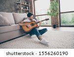 Small photo of Photo of mixed race guy sitting floor leaning sofa hold acoustic instrumental guitar playing new written song sound signing creative talented person flat loft living room indoors