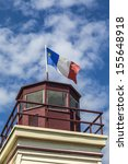 Small photo of An Acadian flag on top of a lighthouse in rural Prince Edward Island, Canada