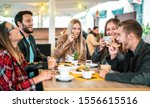 Small photo of Friends group drinking cappuccino at coffee bar - People talking and having fun together at fancy cafeteria - Friendship concept with happy guys and girls at restaurant cafe - Warm bulb light filter